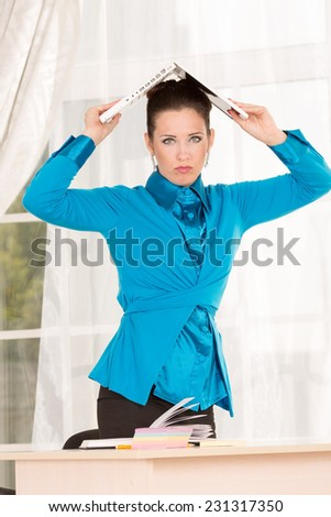 Young woman holding a laptop above his head. Stress in the workplace. A lot of things. Do not have time until the end of the year. The reporting period. Accounting delivers report. Exam tomorrow. End. - stock photo