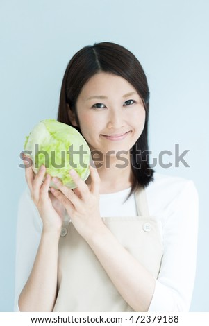 Young woman holding a lettuce against light blue background
