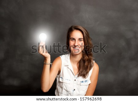 young woman holding a lightbulb in front of chalkboard - stock photo