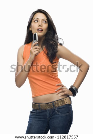 Young woman holding a mobile phone and thinking