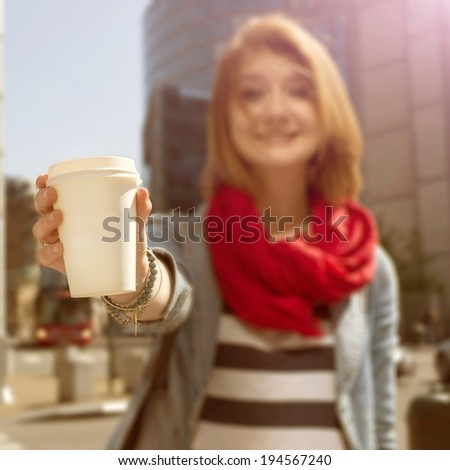 Young woman holding a paper cup and smiling - stock photo