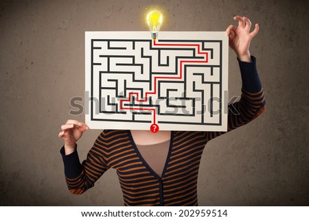 Young woman holding a paper with a labyrinth on it in front of her head