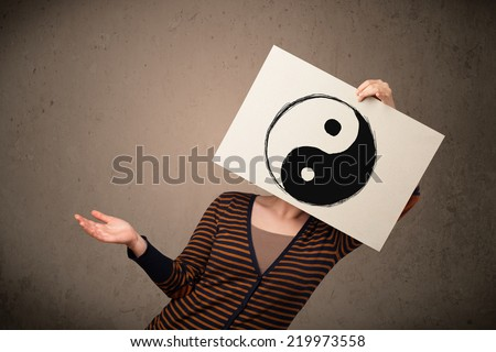 Young woman holding a paper with a yin-yang symbol on it in front of her head - stock photo