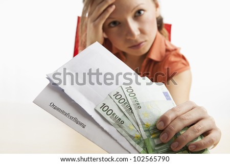 Young woman holding a penal institution and money in her hand - stock photo