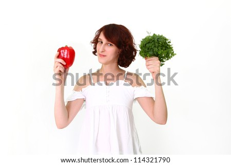 Young woman holding a pepper, dill, parsley - stock photo