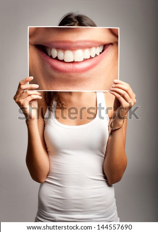 young woman holding a picture of a mouth smiling - stock photo