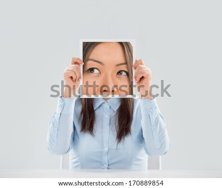 Young woman holding a picture of eyes in front of her face - stock photo