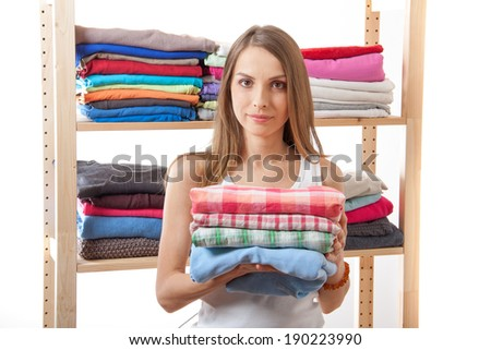young woman holding a pile of clothes, isolated on white background - stock photo
