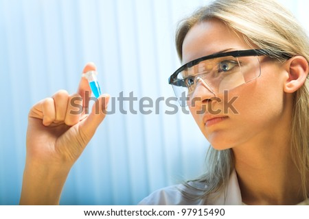 young woman holding a plastic test tube - stock photo