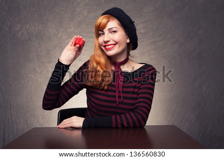 young woman holding a red dice and smiling on grunge background - stock photo