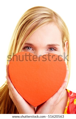 Young woman holding a red heart in front of her face