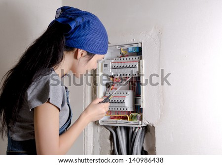Young woman holding a screwdriver looking at an open electrical box and checking the circuit breakers