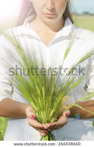 Young woman holding a sheaf of wheat closeup - stock photo