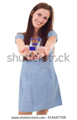 Young woman holding a small shopping cart, isolated, focus on the cart - stock photo