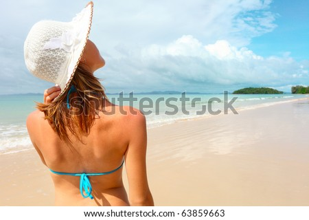 Young woman holding a straw hat and looking to a blue sky - stock photo