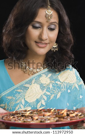 Young woman holding a traditional Diwali thali and smiling - stock photo