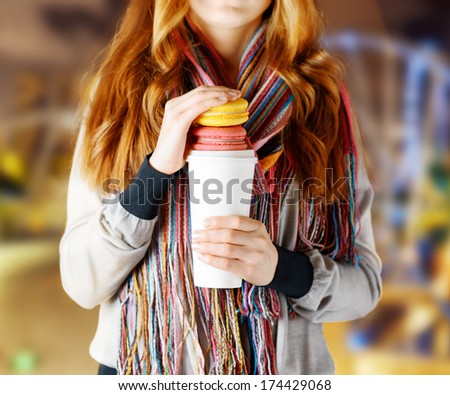 Young woman holding a tumbler of coffee.