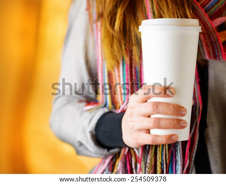 Young woman holding a tumbler of coffee in cafe and enjoying the aroma of coffee. Woman in fashionable colorful striped scarf. Hipster style. - stock photo