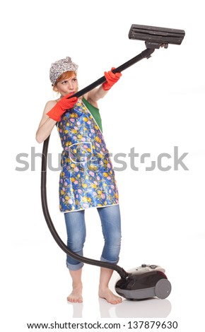 young woman holding a vacuum cleaner like a rifle and aiming, isolated on white background - stock photo