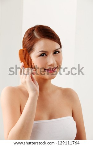 Young woman holding a wooden comb - stock photo