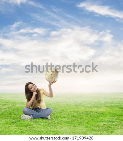 young woman holding a world globe sitting on a meadow - stock photo
