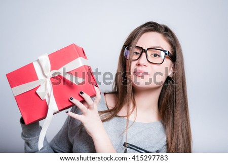 young woman holding a wrapped gift, closeup isolated on gray