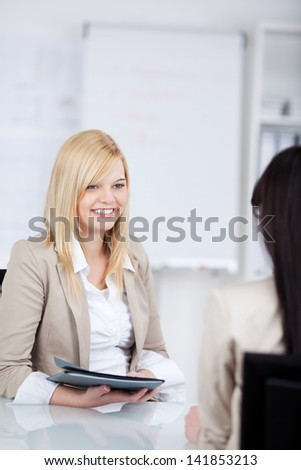 young woman holding an application folder in an interview in the office