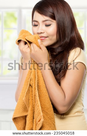 young woman holding and smelling the fresh clean laundry - stock photo
