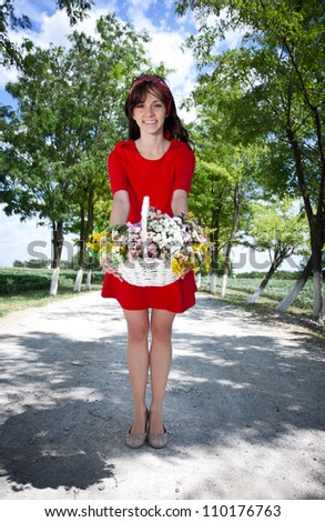 young woman holding basket with flowers outside