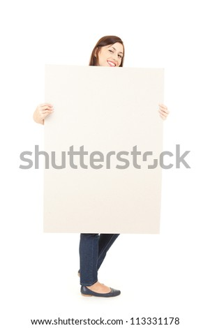 young woman holding blank poster, ful length, white background - stock photo