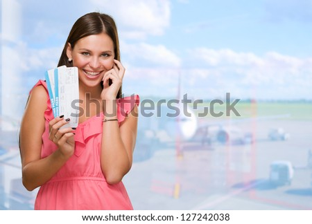 Young Woman Holding Boarding Pass at the airport - stock photo