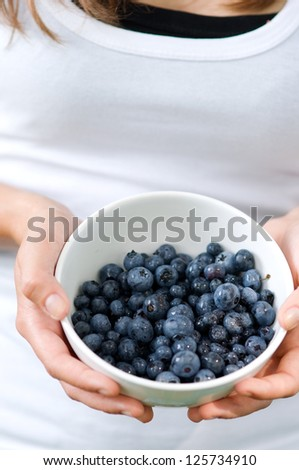 Young woman holding bowl filled blueberries - stock photo