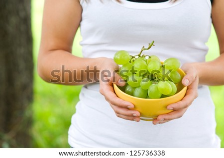 Young woman holding bowl with grapes - stock photo