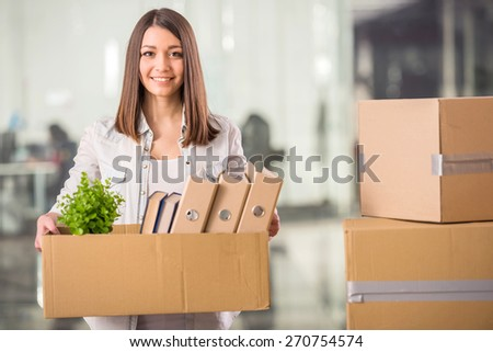 Young woman holding box with things in office. - stock photo