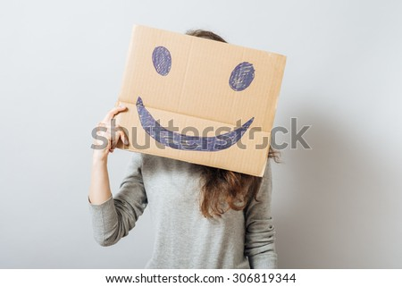 Young woman holding cardboard smiley. On a black background. - stock photo