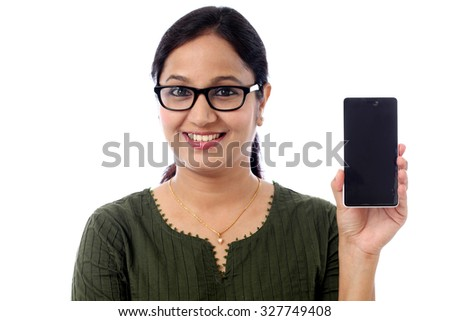 Young woman holding cellphone against white background - stock photo