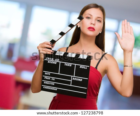 Young Woman Holding Clapper Board, indoor - stock photo
