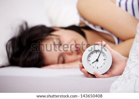 Young woman holding clock while sleeping in bed
