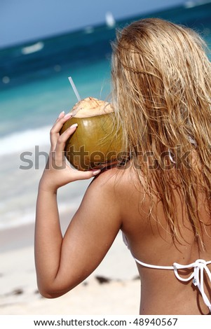 Young woman holding coconut on tropical beach - stock photo