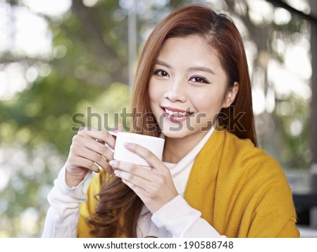 young woman holding coffee cup smiling looking at camera - stock photo