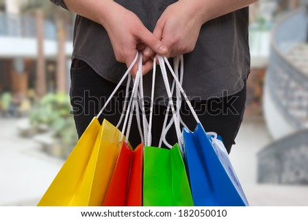 Young woman holding colored shopping bags in a shopping mall in her hand