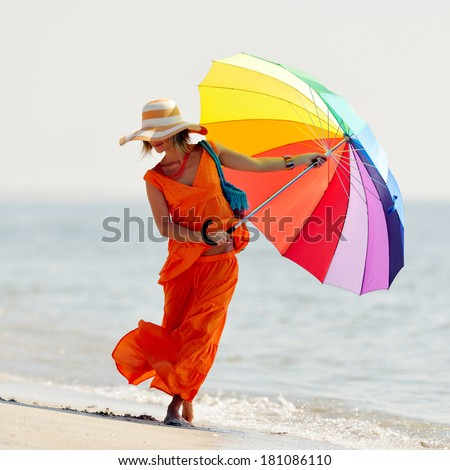 young woman holding colorful umbrella on the beach in summer - stock photo