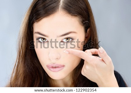 Young woman holding contact lens on finger in front of her eye - stock photo
