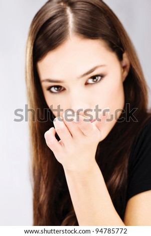 Young woman holding contact lens on finger in front of her face - stock photo