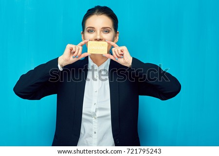 Young woman holding credit card against mouth. Blue wall back.