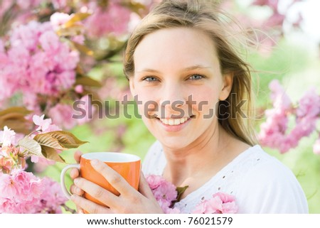 Young woman holding cup ot hot drink outdoor - stock photo