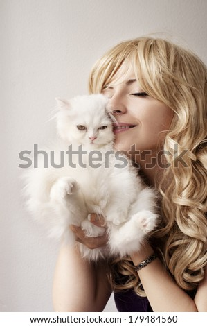 Young woman holding cute white kitten - stock photo