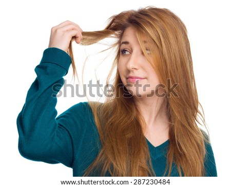 Young woman holding damaged long hair the hand and looking at split ends, isolated on white background  - stock photo
