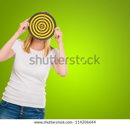 Young Woman Holding Dartboard In Front Of Face On Green Background - stock photo
