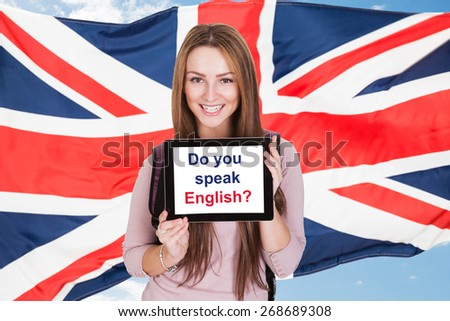 Young Woman Holding Digital Tablet Asking Do You Speak English In Front Of British Flag - stock photo